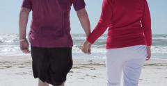 Senior couple hold hands walking on beach - 4K UHD slow motion - stock footage