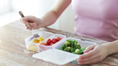 Close up of woman's hands eating vegetables from container - stock footage