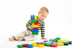 Little cute boy playing with building blocks. Isolated on white. Stock Photos