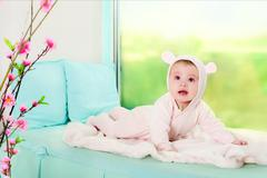 Little girl. child in pink overalls with ears. Stock Photos