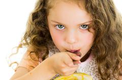 Cute little preschooler girl holding a passion fruit half - stock photo