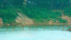 Tourist Walking across Bamboo Bridge in Laos Stock Footage