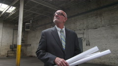 Business man with architecture plans - stock footage