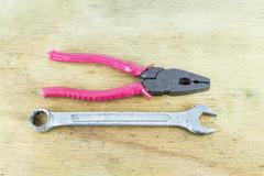 Metal pliers and wrench tools on wood background - stock photo
