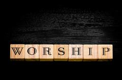 Stock Photo of Word Worship.Wooden small cubes with letters isolated on black background.Con