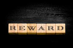 Word Reward. Wooden small cubes with letters isolated on black background.Con Stock Photos