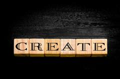Word Create. Wooden small cubes with letters isolated on black background.Con Stock Photos