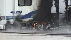 Flaming Tire Of Smoking RV Wreckage Stock Footage
