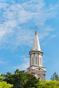 High tower turret of the church under blue sky Stock Photos