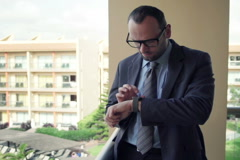 Stock Video Footage of Young businessman with smartwatch while standing on terrace NTSC