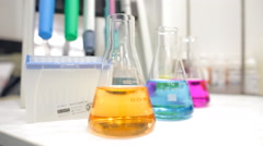 Chemistry laboratory glassware with colour liquids in them Stock Footage