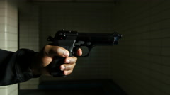 Hand firing a gun in a darp place Stock Footage