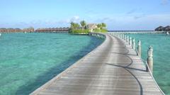 Walking down the wooden jetty towards luxurious ocean villas Stock Footage