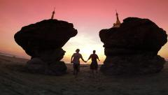Happy couple run to the sunset at Ngwe Saung beach Stock Footage