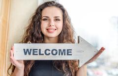 Young woman holding arrow sign Stock Photos