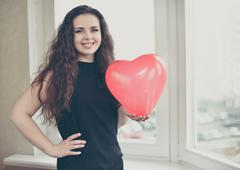 Attractive caucasian woman holding a baloon heart Stock Photos