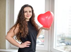 Attractive caucasian woman holding a baloon heart - stock photo