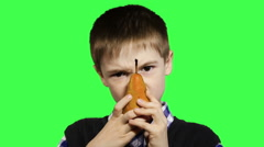 Cheerful boy close-up eats a pear on a green background, 1080p HD video Stock Footage