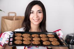 Beautiful woman holding hot roasting pan with cookies - stock photo