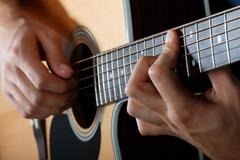Man performing song on acoustic guitar Stock Photos
