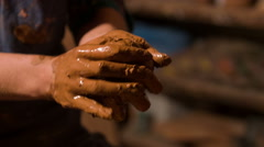 Selective focus on hands of potter standing holding little piece of loam - stock footage