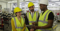 Male and female warehouse workers discussing business logistics in slow motion Stock Footage