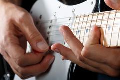 Hands of man playing electric guitar closeup Stock Photos
