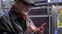 Older man text messaging while riding subway train, close up Stock Footage
