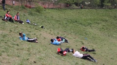 Kids playing and rolling down a grass slope in the park Stock Footage