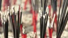 Incense sticks, black and red alternately embroidered on joss Stock Footage