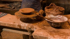 Nice smiling potter working near wooden pail with loam - stock footage