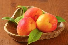 Three ripe apricots in wooden bowl - stock photo