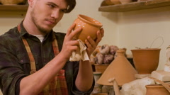 Checking work. Potter wearing apron standing near shelve Stock Footage