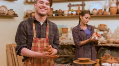 Two potters wearing aprons standing near shelves with different kinds of crocker - stock footage
