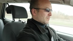 Serious middle age man in glasses drive a car Stock Footage