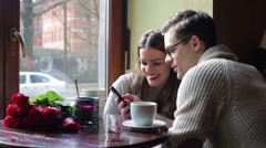 Happy couple sitting in the cafe and looking on the cellphone Stock Footage