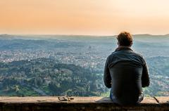 unidentified tourist rests on parapet in Fiesole, Florence - stock photo