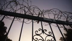 Razor wire on steel fence/gate, panning shot dusk Stock Footage