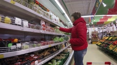 Beautiful young woman shopping for fruits and vegetables in produce department - stock footage