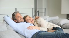 Mature couple relaxing together in couch Stock Footage