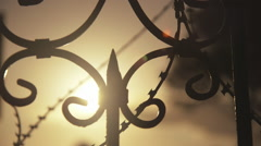 Razor wire on steel gate of old masion sunset back light Stock Footage