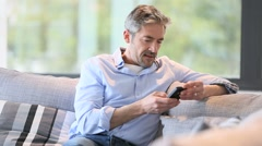 Mature man sitting in sofa and talking on phone Stock Footage