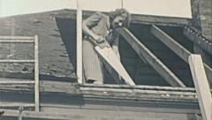 USA 1941: woman working as a carpenter in the roof of an house Stock Footage