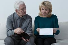 Aged couple analyzing unpaid bills - stock photo