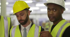 Multi-ethnic workers at a shipping warehouse check stock levels and inventory. Stock Footage