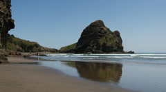 Surfer walking at Piha beach Stock Footage