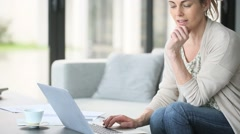 Middle-aged woman working from home on laptop computer Stock Footage