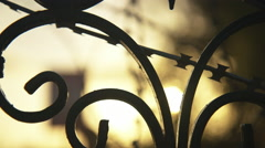 Razor wire on steel gate of old masion sunset back light silhouettes. Stock Footage