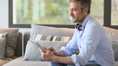 Mature man at home websurfing on digital tablet Stock Footage