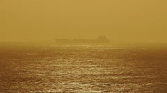 Sunset sea horizon hazy atmosphere container ship silhouette Stock Footage